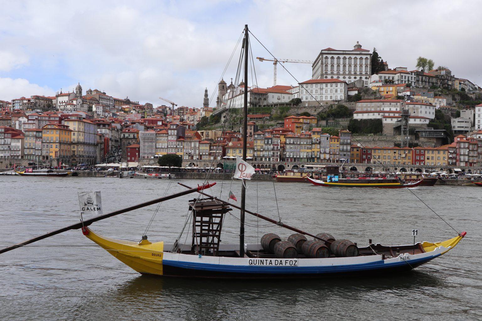 Reproducción de los barcos que transportaban el vino. Al fondo, Oporto. Tour vinos Oporto.